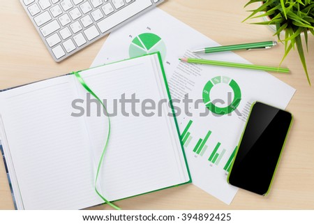 Office desk workplace with smart phone, charts and notepad on wooden table. Top view with copy space