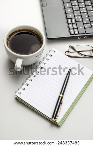 Office desktop with coffee, notepad and glasses. From above - stock photo