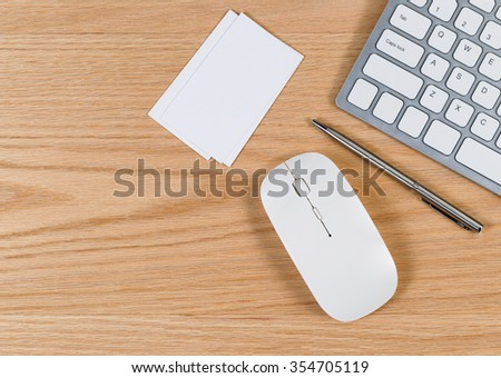 Office desktop with computer keyboard, pen, mouse and blank business cards. Real red oak wooden surface.  - stock photo