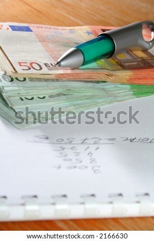 Office desktop with pen, book and money - stock photo