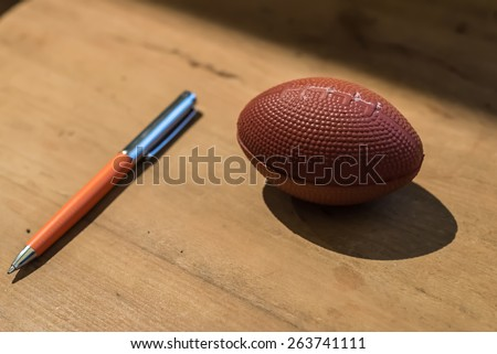 Office elements squeeze ball for stress and a orange pen. - stock photo