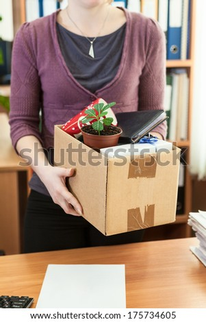 Office employee with collected in a box things standing near desktop - stock photo