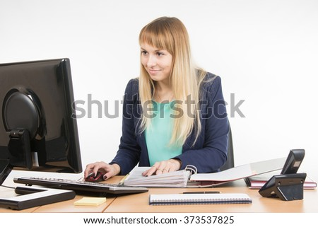 Office employee working at the computer and a folder of paper documents