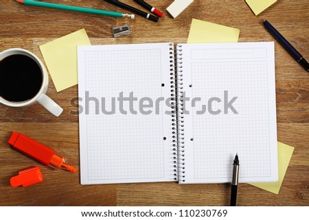Office equipment such as opened notebook, pen, highlighter, cup of coffee, pencil, sticky notes and other on bright wooden office desk. - stock photo