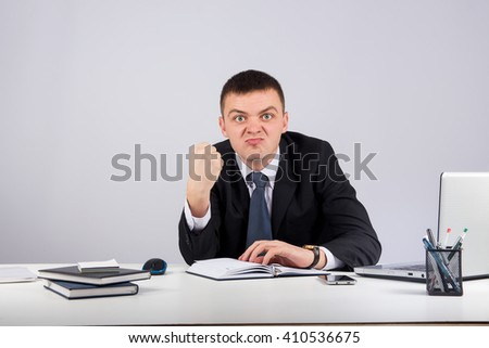 Office, finances, internet, business, success concept-Portrait of a young angry businessman showing you his fist on gray background - stock photo