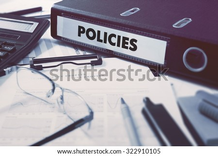 Office folder with inscription Policies on Office Desktop with Office Supplies. Business Concept on Blurred Background. Toned Image. - stock photo