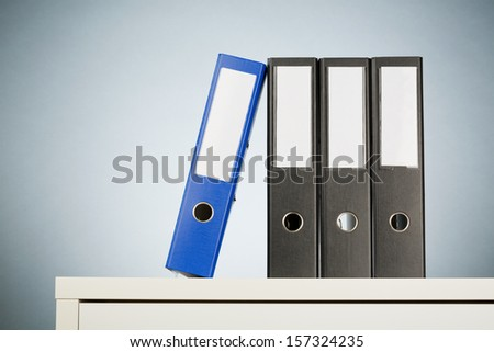 Office folders on a white desk with a light blue background. - stock photo