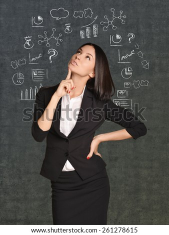 Office girl in a skirt thinks standing at background painted graphics and icons. - stock photo