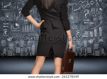 Office girl in skirt with a briefcase looking at figure drawn chalk on the wall. - stock photo