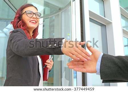 office girl young lady executive officer welcomes a customer with a smile and a  handshake - young charming female CEO gives a warm welcome to a potential client - stock photo