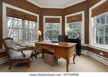 Office in luxury home surrounded by windows - stock photo