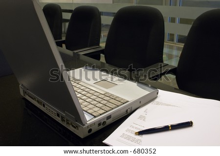 Office Interior 2- A laptop computer, some documents, blank paper and a pen on a black granite table in a conference room