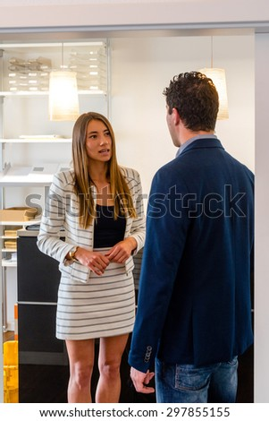 Office interior - a visitor is being picked up by an attractive female receptionist in a modern design environment - might be a startup or a creative agency - stock photo