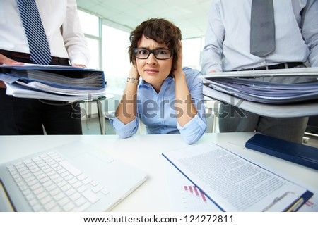 Office lady being scared because of too much paperwork to do - stock photo