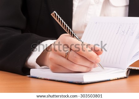 Office lady writing down a week plan in her organizer - stock photo