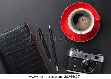 Office leather desk table with camera, supplies and coffee cup. Top view - stock photo