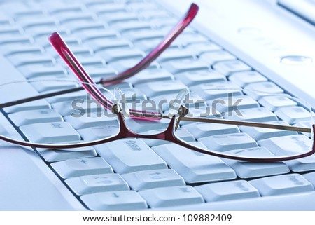 office life. glasses on the computer keyboard