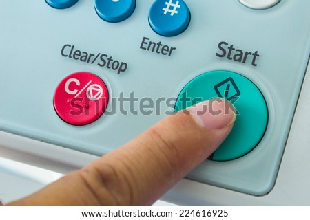 Office life, hand pressing start button on fax, copy machine - stock photo