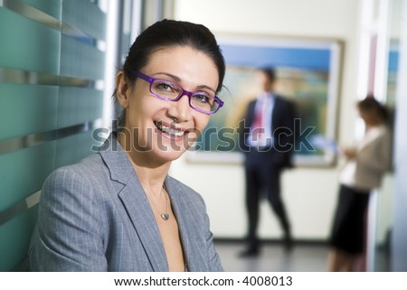Office life: young business woman looking at the camera smiling