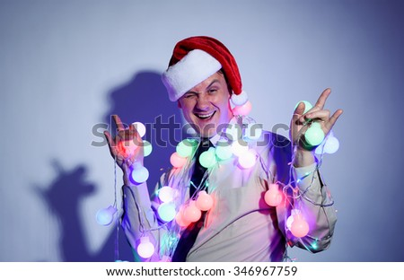 Office man in a Santa Claus red cap with colored garlands - stock photo