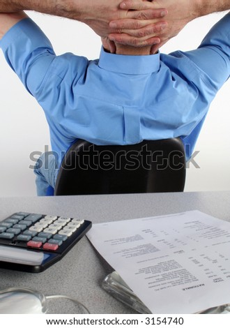 Office man sat at desk with back to camera. - stock photo
