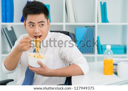 Office manager enjoying instant noodles at his workplace - stock photo