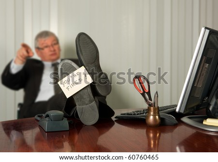 Office manager firing an employee with a yellow sticky note on his shoe - stock photo