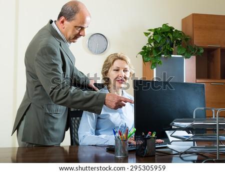 Office manager scolding elderly secretary for mistake - stock photo