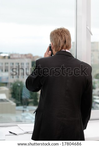 office manager talking by mobile-phone - stock photo