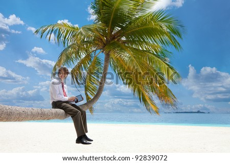 Office manager with tablet pc sitting on palm tree on the Maldivian beach and looking at camera smiling - stock photo