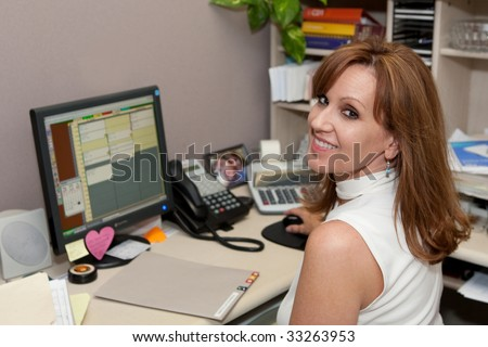 Office manager working on patient files at computer - stock photo