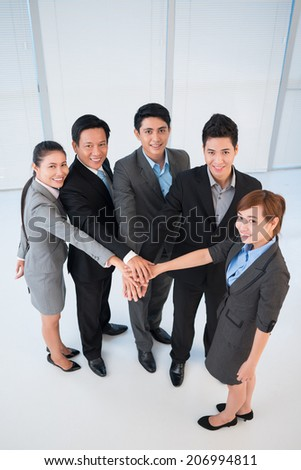 Office managers stacking their hands as a symbol of unity - stock photo