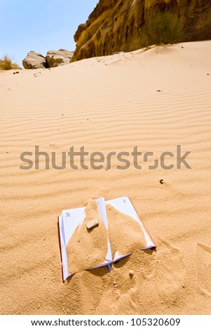 office note book in red sand of Wadi Rum desert in Jordan - stock photo