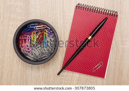 Office notebook and office paper clips on the desk.