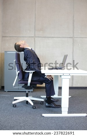 Office occupational disease prevention - business man exercising at workstation - stock photo