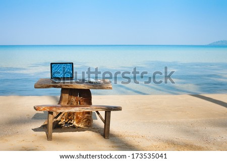 office on the beach, computer and table - stock photo