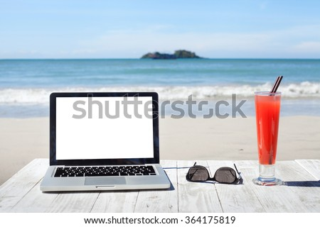 office on the beach, laptop with empty screen, sunglasses and tropical cocktail  - stock photo