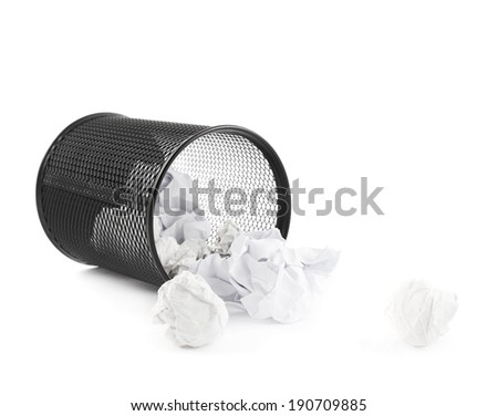 Office paper black trash bin, lying on its side next to crumpled paper, isolated over the white background - stock photo