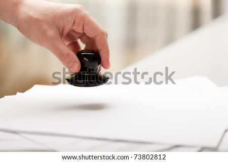 Office paper document stamp in business human hand - stock photo