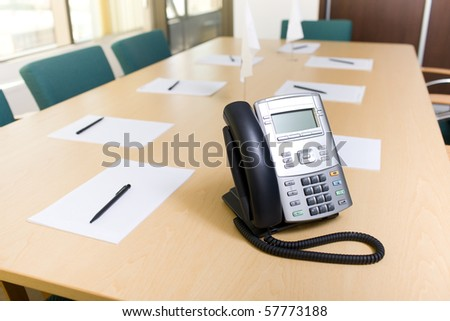 Office phone on table in meeting room - stock photo