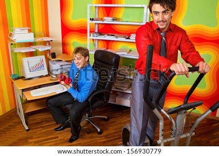 Office portrait of beautiful businesspeople doing exercise at their workplace  - stock photo