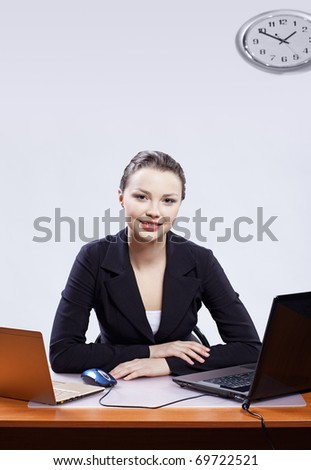 office portrait of beautiful friendly young business woman sitting at her workplace with two laptops on gray