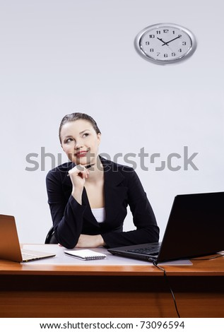office portrait of beautiful happy thoughtful business woman sitting at her workplace with two laptops on gray - stock photo