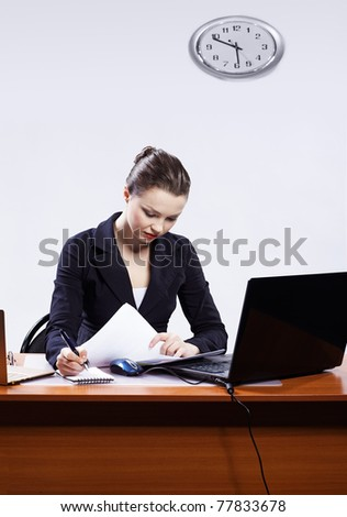 office portrait of beautiful serious concetrated business woman at her workplace with documents and two laptops on gray