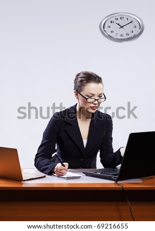 office portrait of beautiful young business woman in glasses sitting at her workplace with two laptops and block note on gray