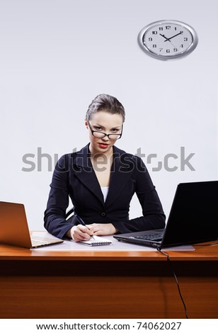 office portrait of beautiful young business woman in glasses sitting at her workplace with two laptops on gray and writing note - stock photo