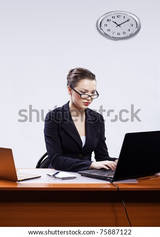 office portrait of beautiful young business woman in glasses sitting at her workplace with two laptops on gray and typing on one of it - stock photo