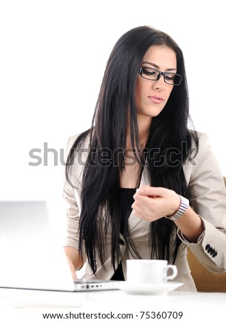 Office portrait of beautiful young business woman looking at her wrist watch - stock photo