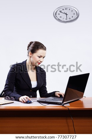office portrait of beautiful young business woman sitting at her workplace with two laptops on gray - stock photo