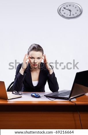 office portrait of beautiful young business woman with headache sitting between tow laptops and massaging her temples - stock photo